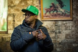 Photo of Film/ TV Director Bim Ajadi wearing a puffa jacket and green baseball cap
