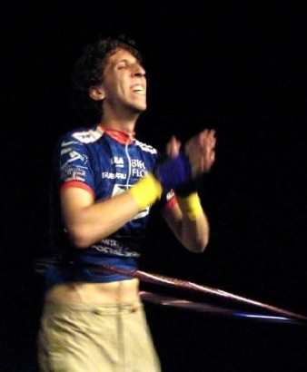 a man in cycling gear spins a hoop around his waist looking gleeful