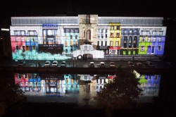 Cork's College of Commerce is lit up with a projection depicting colourful buildings with an Invacar driving down the projected street emitting blue smoke © Clare Keogh