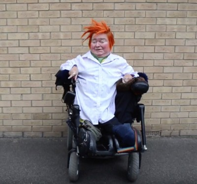Photo of Katherine with orange hair in her wheelchair in front of a brick wall