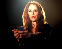 photo of actress with long hair holding out her hands holding a glass