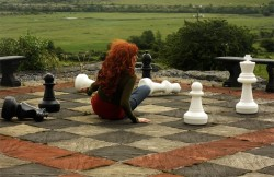 photographer Karen Forrester lies pictured on a giant chess board
