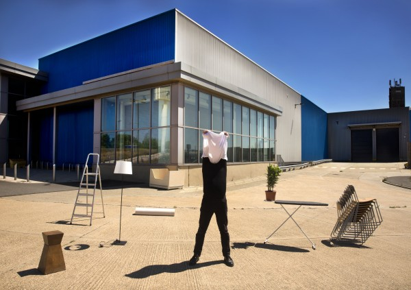 image of the artist Aaron Williamson concealing his face with a white t-shirt, in a forecourt surrounded by everyday objects