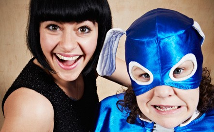 The two performers are looking at the camera. Jess Mabel Jones is wearing a black top and smiling. Jess Thom is dressed as a superhero with a blue cape and blue headdress. She is grimacing.