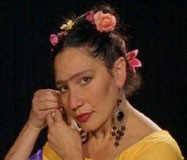 Isolte Avila playing Frida Kahlo. Her hair is braided with roses. She looks at the camera as she inserts a black jewelled earring into her right ear.