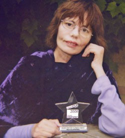 photo of artist Nancy Willis sitting with a film-making award