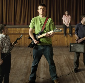 A film poster image for Sons and Mothers. Four performers stand in a stage area, one holds an electric guitar
