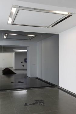 a photo of an almost bare gallery space with a piece of rag on the floor
