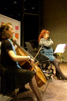 In the foreground a woman plays a cello. Behind her a woman sits in front of a sheet on a music stand