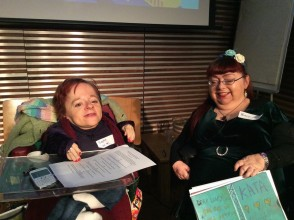 photo of disabled performers Sophie Partridge and Penny Pepper holding scripts for performance on stage at a poetry event
