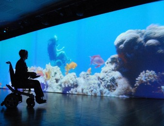 photo of artist sue austin in her wheelchair in front of a huge projection of herself underwater amongst coral