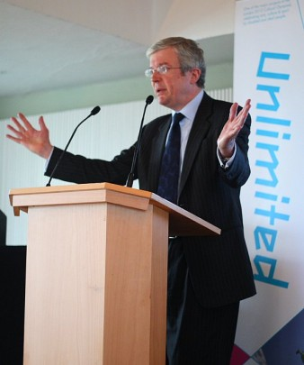 photo of a man in a suit speaking at a lectern - he's spreading his arms out and gesticulating Jon Pratty/dao