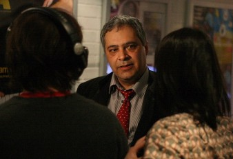A man is seen talking to two people who are seen on either side of him from behind. He's looking thoughtful.