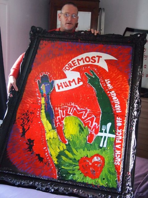photo of the artist Vince Laws holding a large canvas of a green figure reaching out across a red background