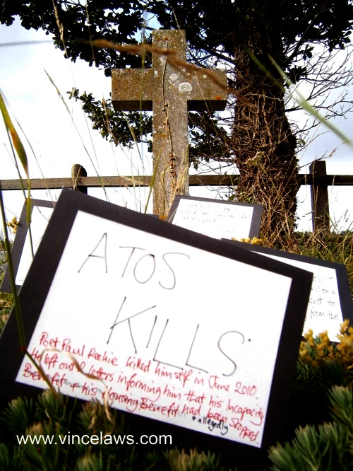 photo of placard with atos kills written on it, standing against a cross in a graveyard