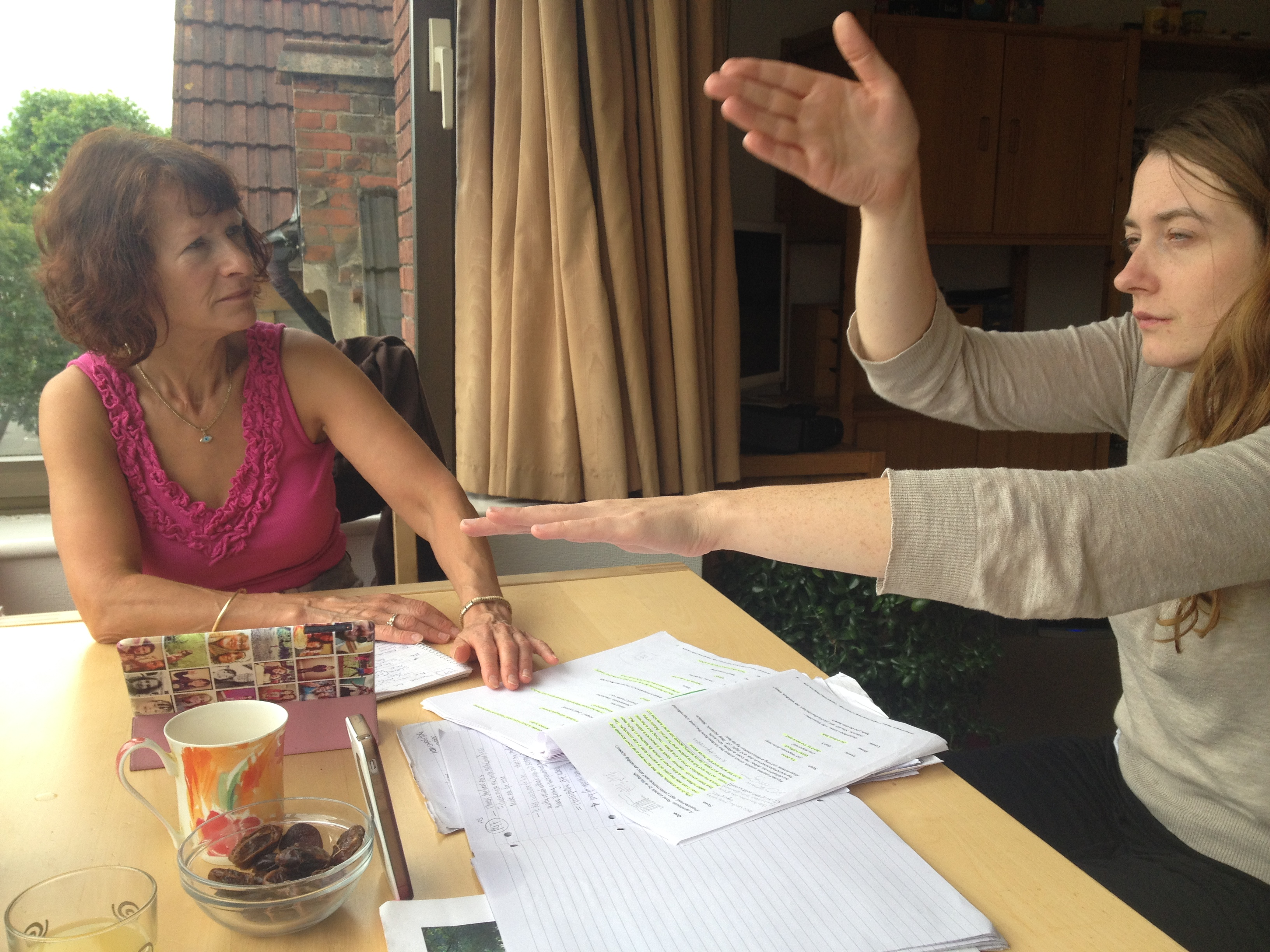 Two women face each other across a table with a script on it, devising sign language interpretation